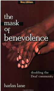 "Image shows the cover of ""The Mask of Benevolence: Disabling the Deaf Community"" by Harlan Lane. A photograph of a pair of hands is on a black background. The hands are making the American Sign Language sign for ""hypocrite""."