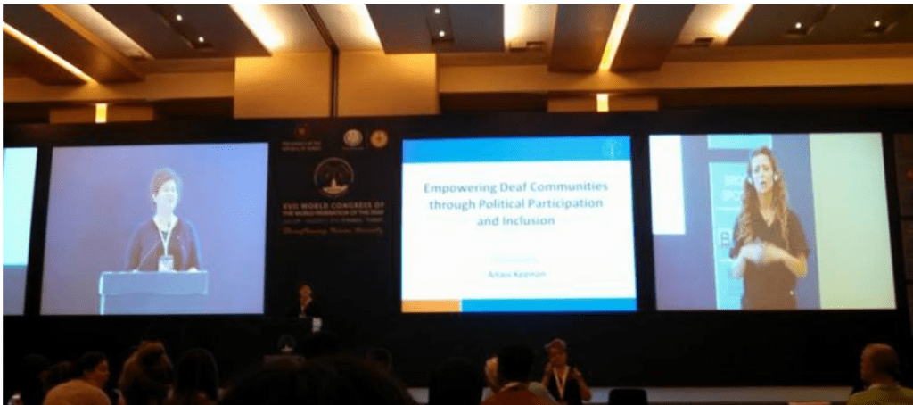 """This photo shows three screens at the front of a conference room. The screen at left shows Anais Keenon presenting. The middle screen shows a power point slide with the presentation title """"Empowering Deaf Communities through Political Participation and Inclusion"""". The right screen shows an interpreter."""