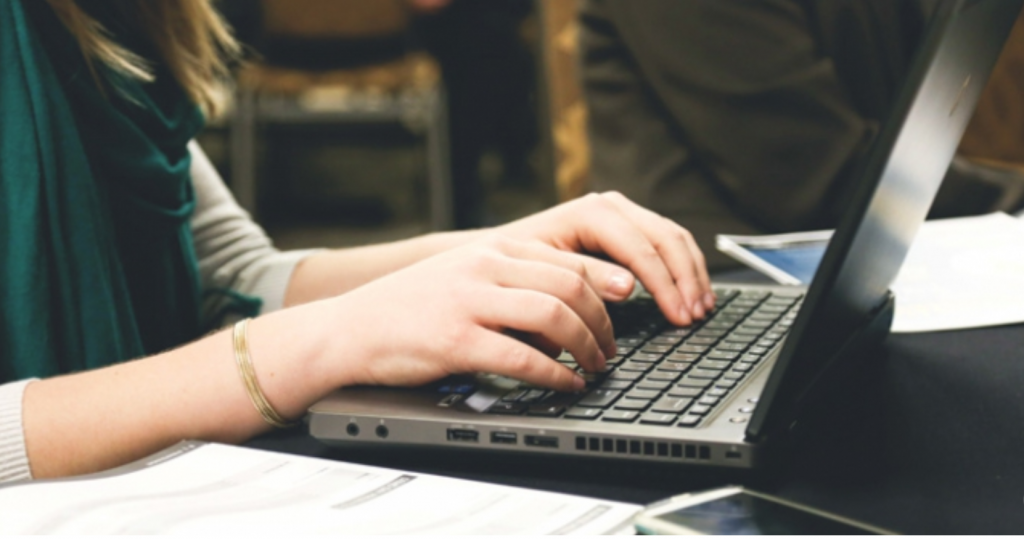 A pair of hands rest on the keyboard of a laptop. The person's face is not visible.