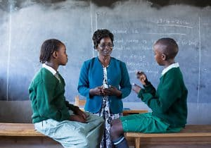 Two students are sitting on top of their desks so that they can face each other. They are both looking toward the teacher who stands in between them. One child is moving his hands. A blackboard is on the wall behind the teacher.