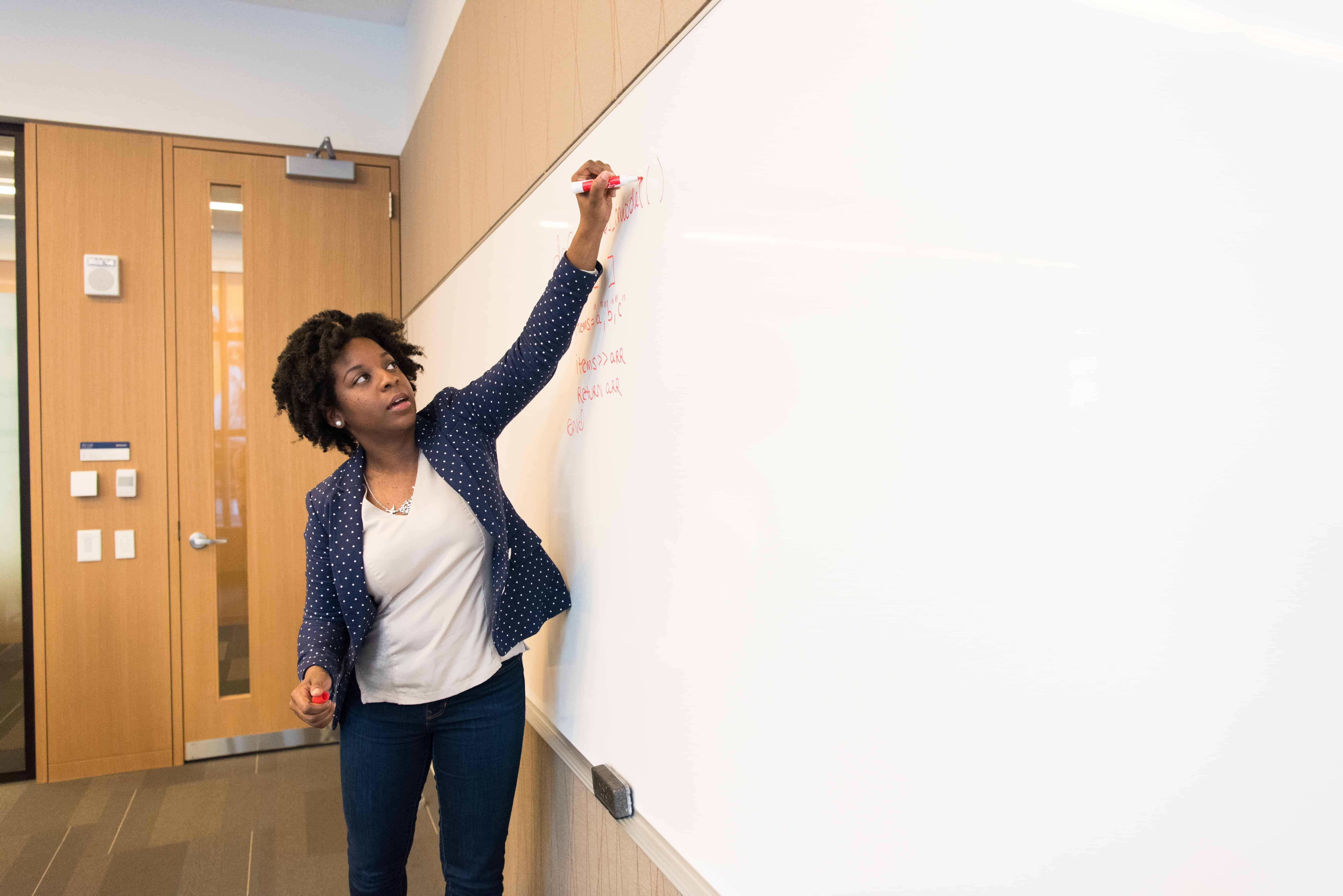 A teacher stands, writing on a white board in the front of a classroom.