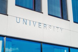 "Lettering on the side of a building says ""University""."