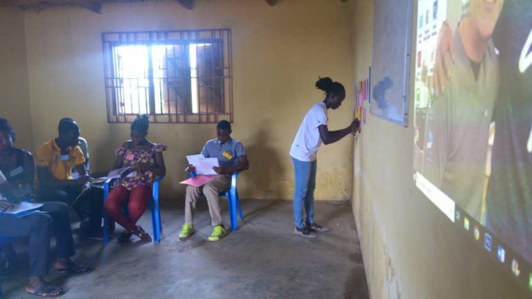 a woman is drawing on a paper on the wall while people watches her