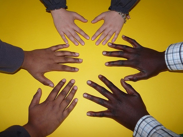 Three pairs of hands in varying skin tones are next to each other in a circle, all laid flat against a yellow surface.