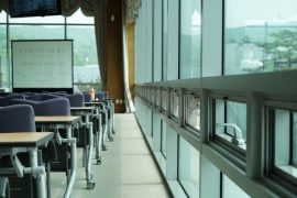 Photo shows rows of empty chairs at tables. At the front of the room is a whiteboard.