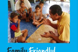 """Cover of """"Family Friendly! Working with deaf children and their communities worldwide"""". A photo on the cover shows a deaf adult teaching sign language to a deaf child while other family members watch."""