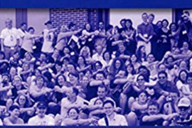 """Cover of the book entitled """"Many Ways to be Deaf: International Variations in Deaf Communities"""". Below the title is a photo that shows a large group of Deaf people. Many people in the picture have one hand on the shoulder of the person next to them."""