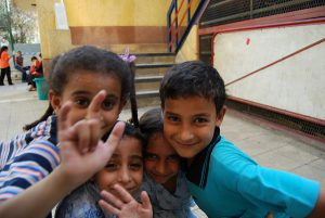 "A group of four children of varying ages cluster together, smiling at the camera. One child makes the sign for ""I love you""."