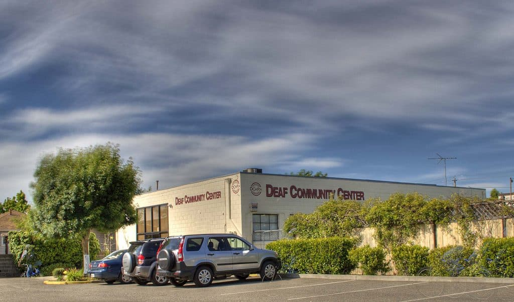 "The corner of a large two-floor building shows lettering on two sides that both say ""Deaf Community Center"". A few cars are parked in front. No people are in sight."