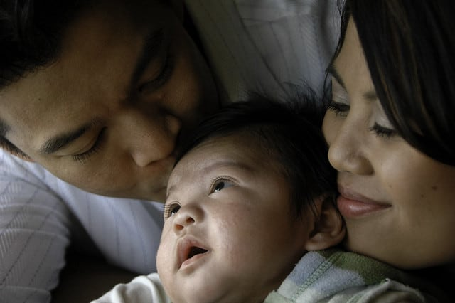 Photo shows a close up of the faces of a man, a woman, and their baby in between them. The father is kissing the head of the baby as the mother looks on with a smile.