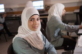 Teen girls in hijabi are seated in front of computers at school. One girl faces the camera with a smile.