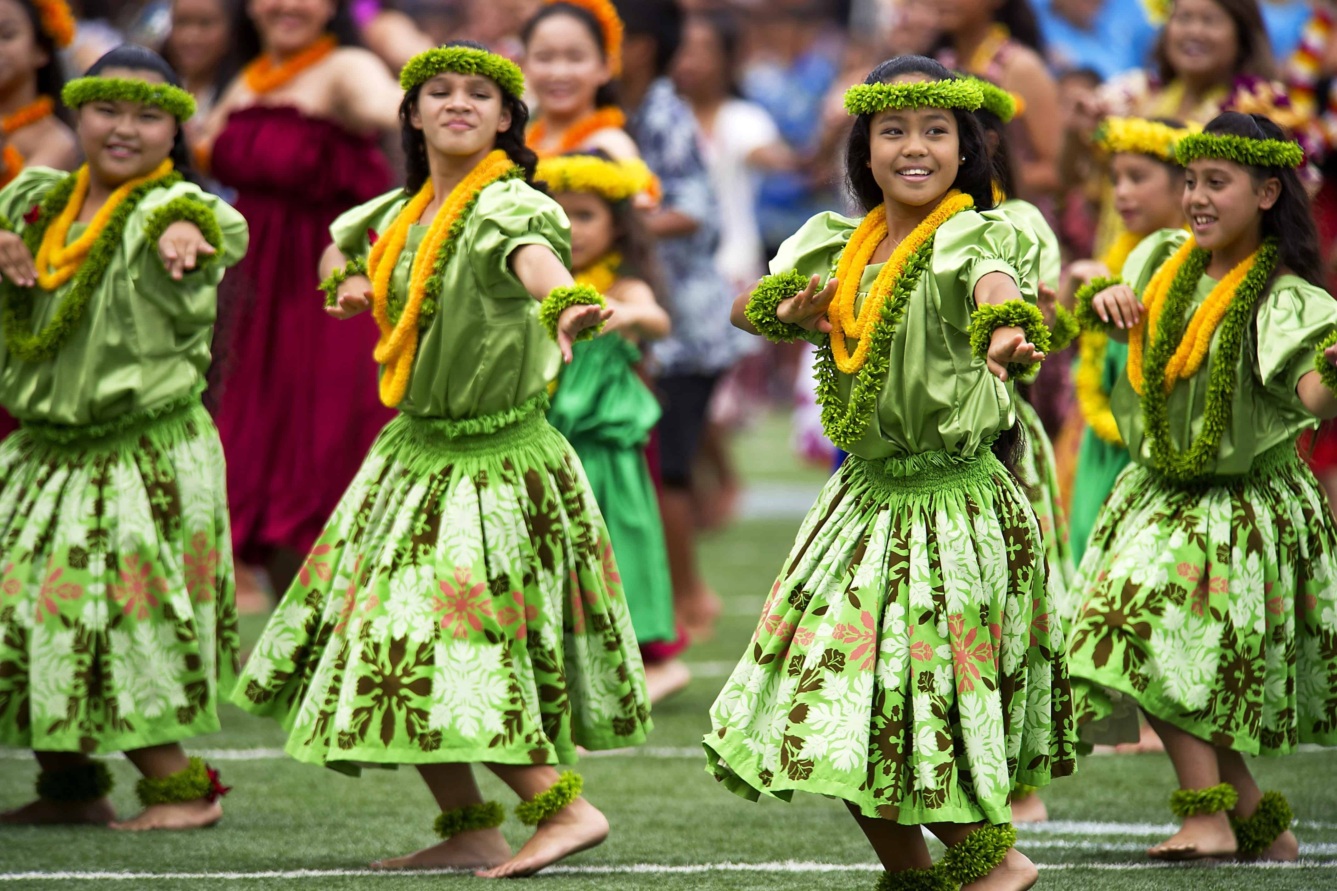 Several girls wearing green dresses and yellow leis are dancing.