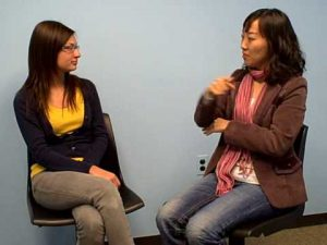 Screenshot from a video shows one woman signing to another woman.