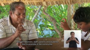 Screenshot from a video about Kiribati Sign Language Awareness week. An older man is signing with a young boy. English captions are on the bottom of the screen. Also, a box in the lower right corner shows an interpreter using Kiribati Sign language.