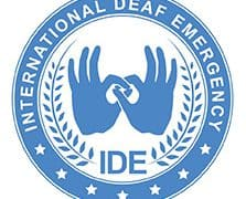 Logo for International Deaf Emergency shows the name of the organization inside the rim of a circle. In the center of the circle is a pair of hands with thumbs and forefingers forming interlinked circles. The hands are wrapped in a wreath with the acronym IDE at the bottom.