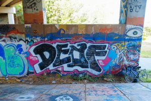 "Large mural with the word ""DEAF"" spray painted in large letters. A large eye is drawn above the right side of the word."