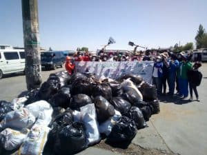 a group of deaf people standing in front of all trash they collected