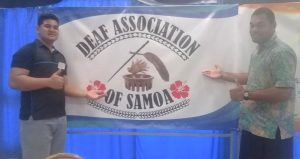 "two men standing next to a logo banner ""Deaf Association of Samoa"""