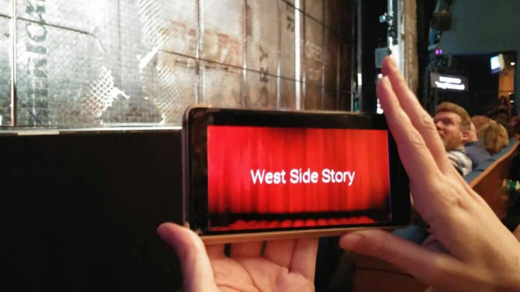 """Photo of a pair of hands holding a phone that says """"West Side Story"""". The phone is being held up in front of a large stage in a live performance theater."""