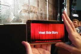 "Photo of a pair of hands holding a phone that says ""West Side Story"". The phone is being held up in front of a large stage in a live performance theater."