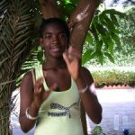 Photo from the African Sign Languages Portal shows a woman signing to the camera. She is outside, in front of a short tree.