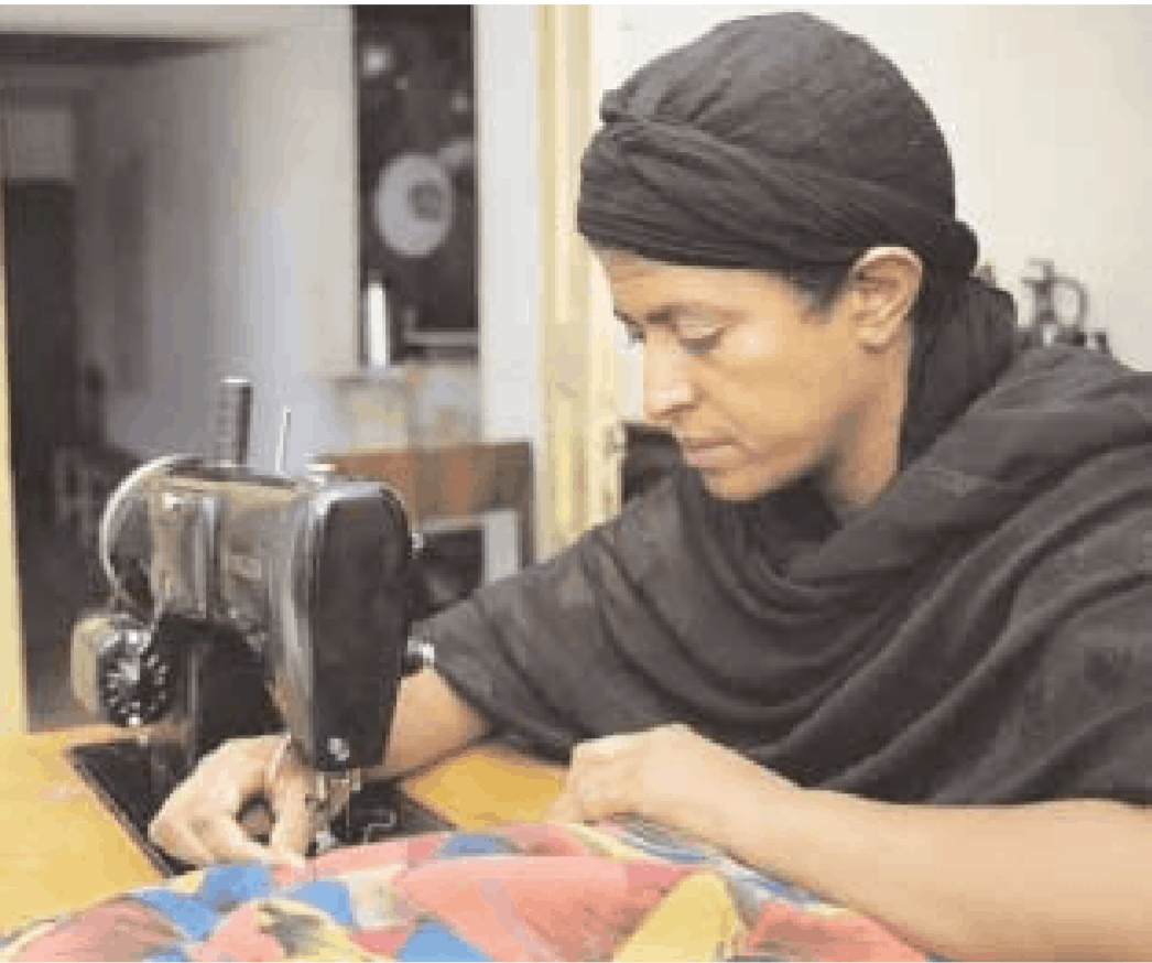 Photo of an Ethiopian deaf woman entrepreneur using a sewing machine.