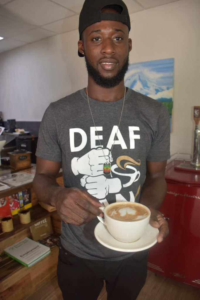 """A man holding a mug of coffee looks at the camera. His T-shirt says """"Deaf"""" and has the image of a pair of hands signing """"coffee"""" on it."""