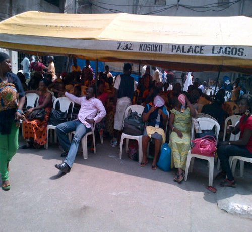Deaf Nigerians are seated together outside in the shade of a long awning. They are members of the Deaf Supporter's Group in Lagos, Nigeria.