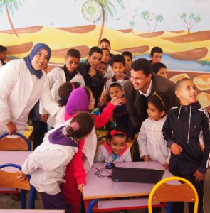 Two adults and a large group of children are clustered around technical equipment on a table.