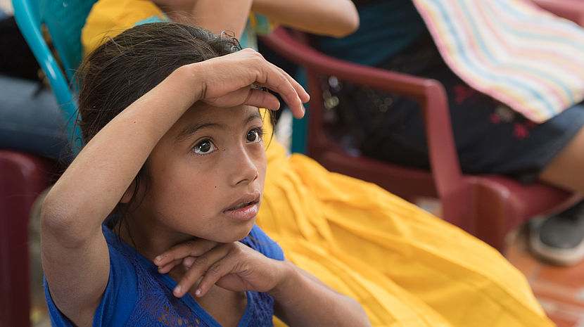A young girl, seated among adults, uses one arm to shield her eyes from the sun.