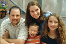 A father and mother with two children all smile at the camera.