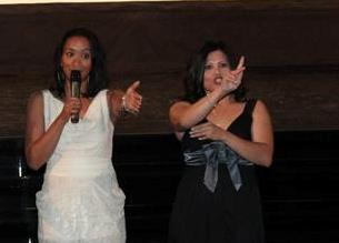 A woman is speaking into a microphone while an interpreter signs next to her, both addressing an audience not shown in the photo.