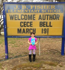 "A young girl stands in front of a school sign holding the book El Deafo. The sign says """"J.B. Fisher Elementary School: Welcome author Cece Bell March 19!"""