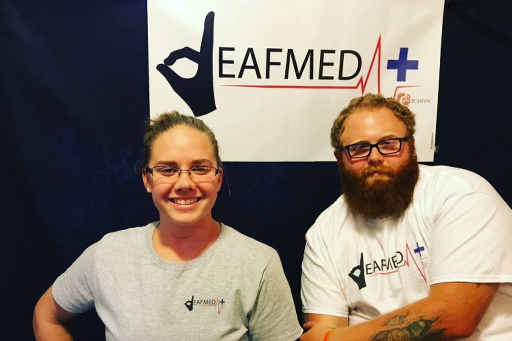 "A woman and a man are looking at the camera. On the wall behind them is a sign that has a logo for DeafMed. The ""D"" is replaced with a drawing of a hand forming the letter D in American fingerspelling. Both people are wearing t-shirts with the same logo for DeafMed."