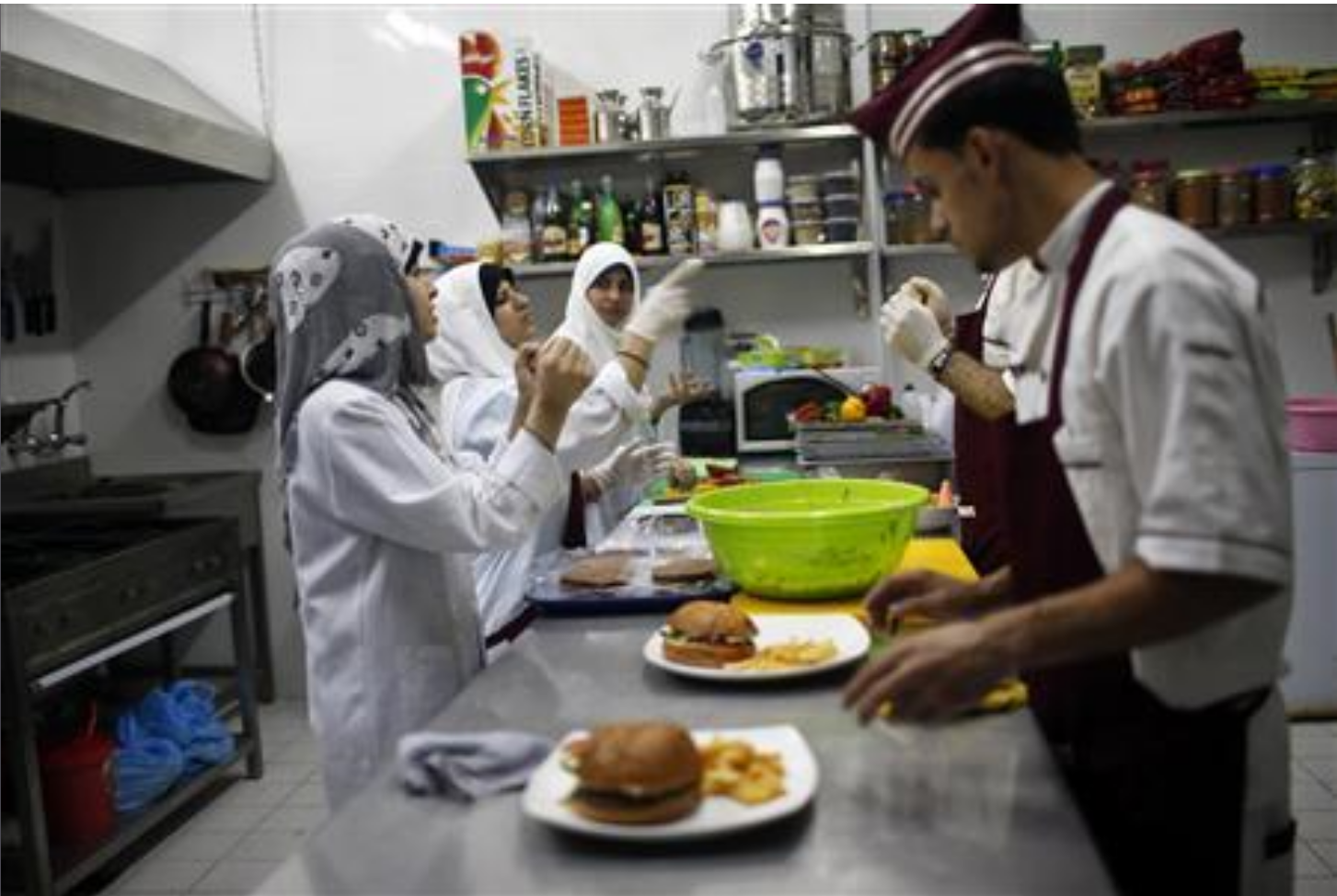 Three hijabi women and two men are working in the kitchen of a deaf restaurant in Gaza. They are signing to each other.