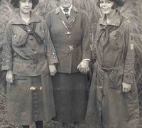 A black and white photo shows three women dressed in Girl Scout uniforms used early in its history.