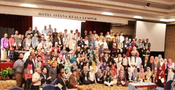 """A group of a large group of people standing or sitting in rows. A sign above them says """"Hotel Estana Kuala Lumpur"""""""