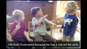 "A video frozen in a scene that shows three young children signing to each other. The subtitle on the screen says ""He feels frustrated because he has a cut on his arm"""