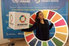 "A woman stands inside a large circle with 17 colors, each representing one of the 17 Sustainable Development Goals (SDGs). She also holds a box with the same SDG logo and the slogan ""The Global Goals for Sustainable Development""."