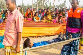"Cover of the publication entitled ""Saving Lives and Leaving No One Behind: The Gaibandha Model for disability-inclusive disaster risk reduction"". The picture on the cover shows two people carrying someone on a stretcher. More people are behind them, watching."