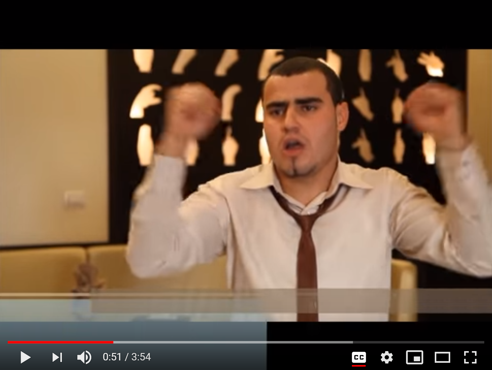 Screenshot taken from a video on deaf equality in Gaza City. Shows a man signing to the camera. Behind him, a tapestry on the wall shows various hand shapes.