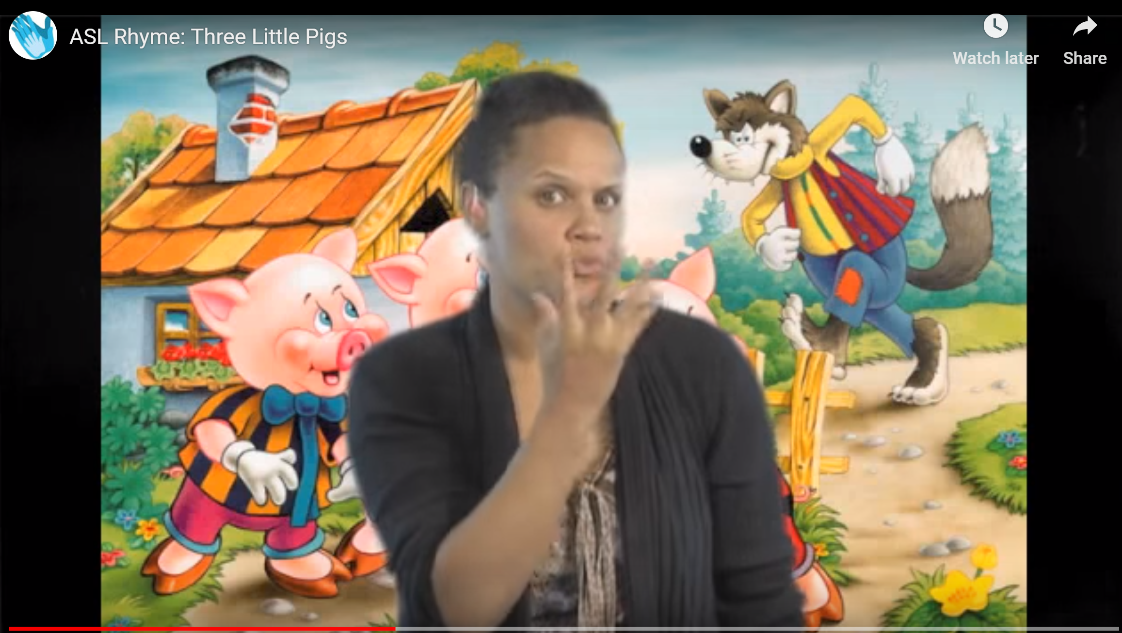 This screenshot of a frozen scene from a video shows a woman signing to the camera. Behind her is a drawing from a children's book that shows three pigs in front of a house. A wolf is walking toward the pigs.