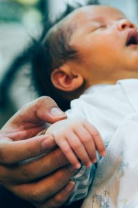 A baby is fast asleep. A large, adult-sized hand gently lifts the baby's hand.