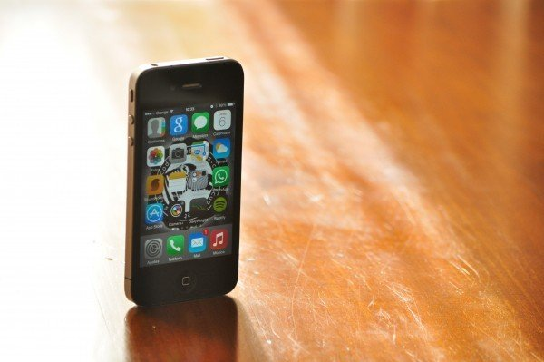Photograph shows a smartphone standing upright on its bottom edge on a wooden surface.