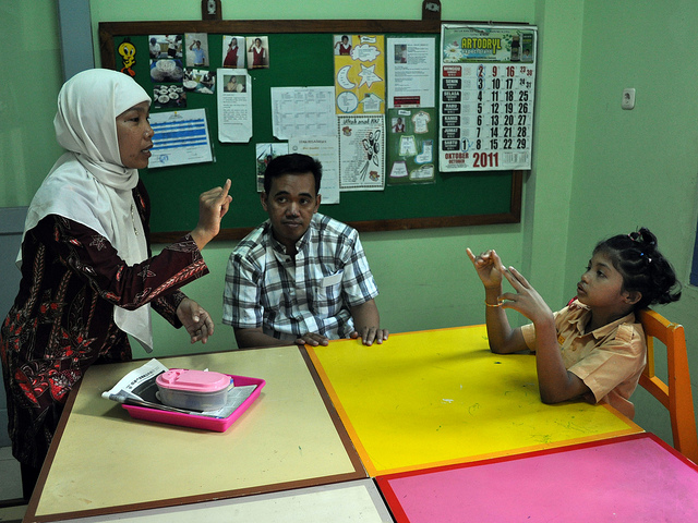 A young girl and a teacher sign to each other across a table while a man watches them.