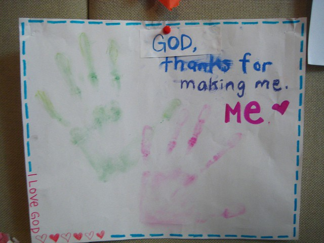 "Photo of a large sheet of paper with a pair of hand prints in green and red. A message is written on the sheet that says ""God, thanks for making me, me."