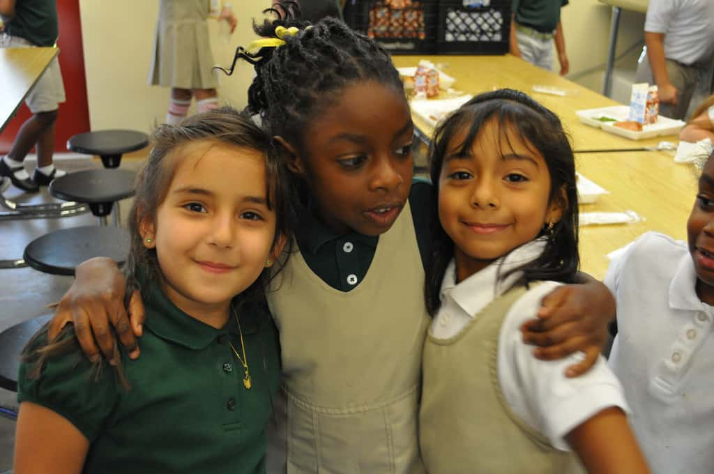 Three school girls stand with their arms around each other. Two are facing the camera with a smile, the girl in the middle looks more solemn and is looking at one of the other girls.