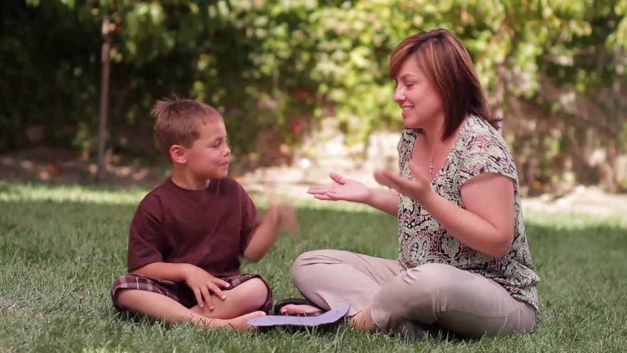 A young boy sits on the grass with his mother. The child and his mother are using sign language.