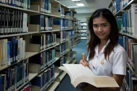 A young woman stands in a library with a book in her hand.