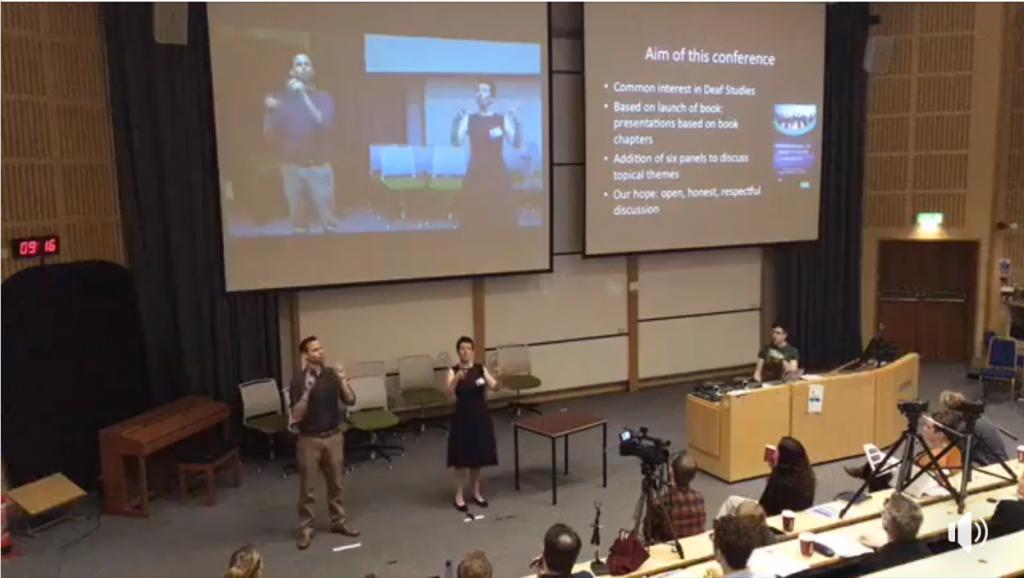 Screenshot of a video of a conference. Three people are on stage, with two projector screens behind them. Two are signing in different signed languages.